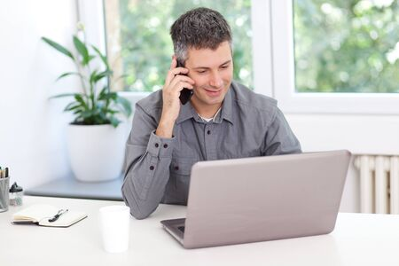 Beautiful young man working on computer and talking on phone