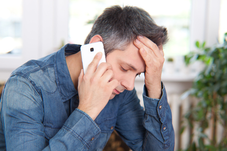 Man getting bad news on the phone