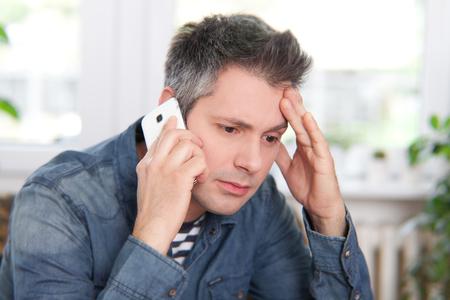 Mann, der eine schlechte Nachricht am Telefon
