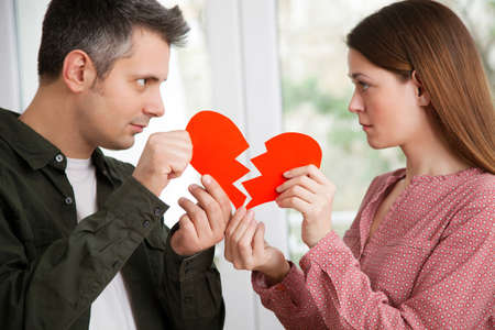 Young couple holding ripped heart shaped paper, shallow depth of field Archivio Fotografico