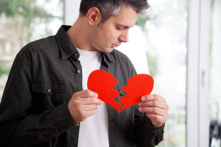 Sad young man holding ripped heart shaped paper
