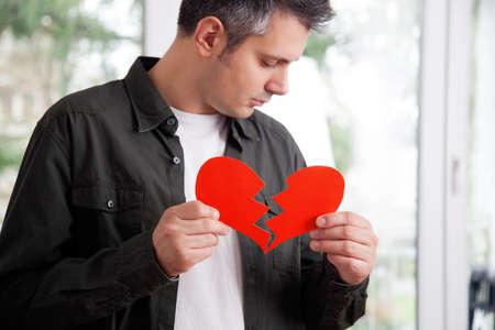 Triest jonge man die gescheurd hartvormige papier