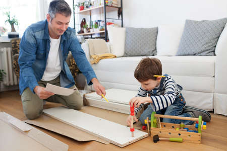 Father and son assembling furniture at home 免版税图像 - 69118072