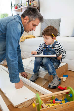 Father and son assembling furniture at home