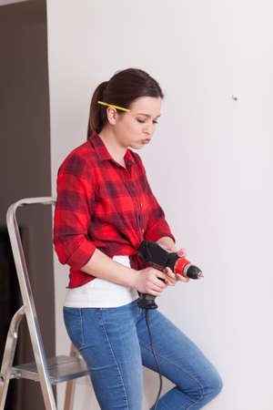 Beautiful young woman holding a drill