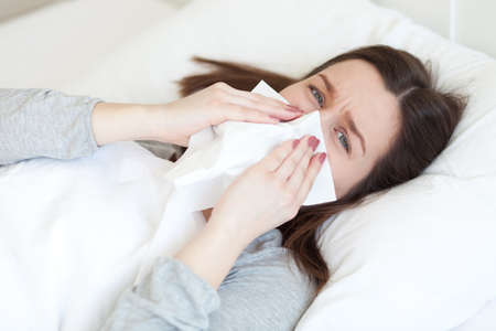 Young woman lying sick in bed