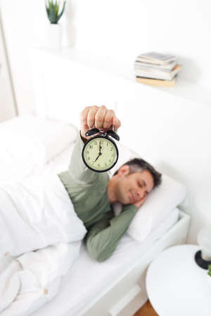Man extremely annoyed by the alarm clock, shallow depth of field, focus on foreground