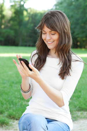 Young beautiful woman using cell phone outdoor