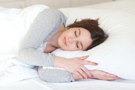 Beautiful young woman asleep, on white background 免版税图像