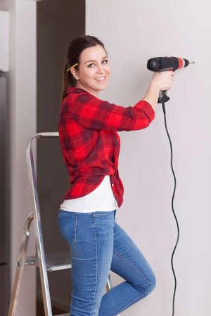 Beautiful young woman using a drill 免版税图像