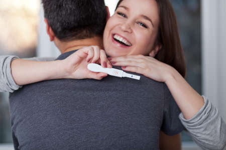 Delighted young woman holding pregnancy test and hugging her man, shallow depth of field