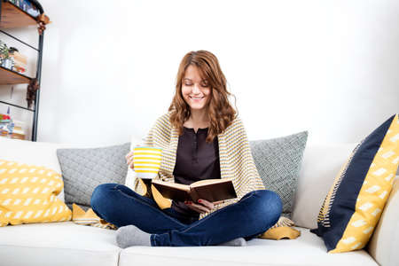 Beautiful young woman relaxing at home, reading a book