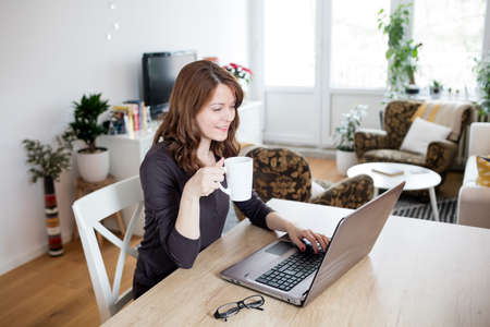 Beautiful young woman working on laptop at home 免版税图像