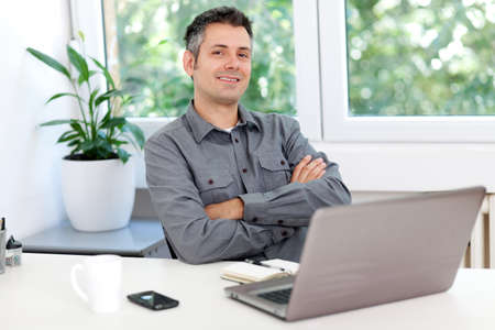 Image of a confident young man sitting at working desk