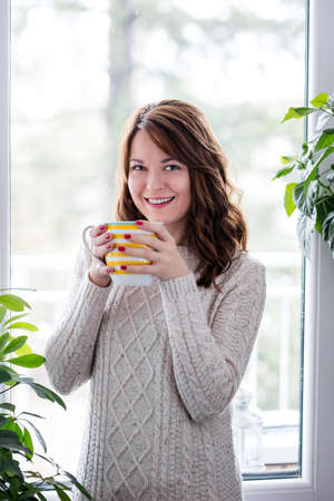 Beautiful young woman sitting by the window having hot drink