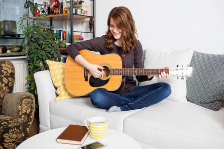 Beautiful young woman sitting on couch, playing a guitar