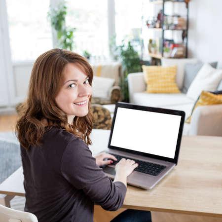 Beautiful young woman using laptop, blank screen