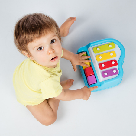Baby boy playing toy piano