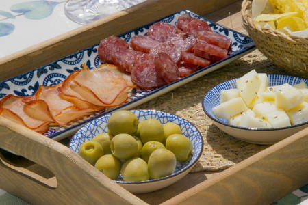 Close up of a wooden tray filled with spanish tapas with olives, cheese, smoked sausage, slices of ham and a bowl of crisps
