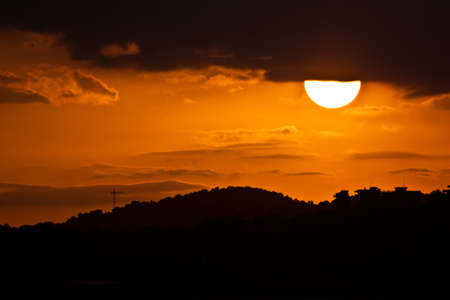 observed: Sunset landscape, half sun and observed under a mountain Stock Photo