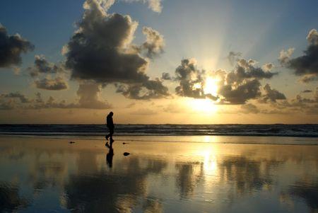 Man walking on the beach at Sunset