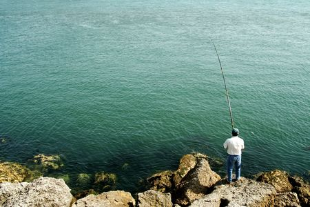 Men fishing by the ocean photo