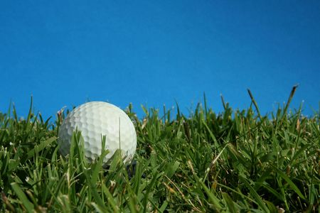 golf ball lying in green grass with blue sky