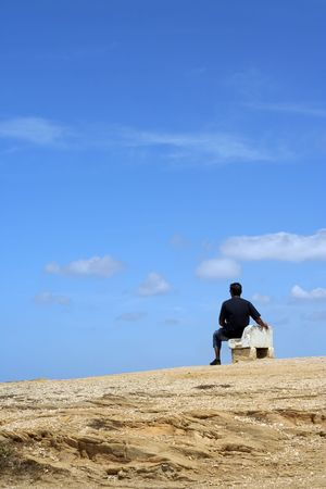 man sitting on a bench with blue cloudy sky