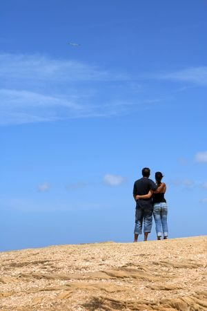 Young couple looking up together with sky background