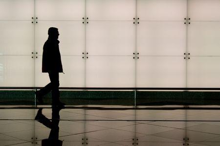 Man walking through an airport terminal Stock Photo