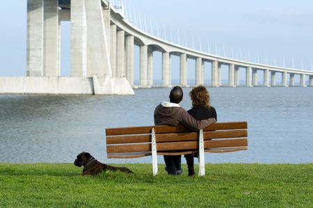 Couple sitting on a bench near the water. photo
