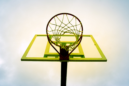 the height of a rim: yellow basketball hoop against the blue sky.