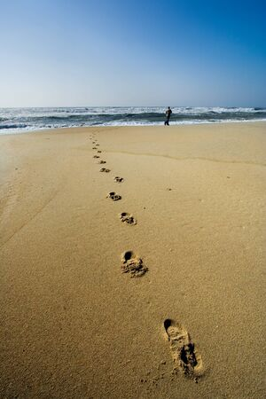 a man walking on the beach with his footprints in the sand along the shore