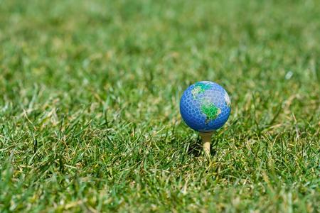 Single earth golf ball lying on green grass photo