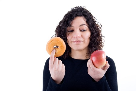 good or bad: an attractive fit girl weighs her options of weather to eat donut or an apple