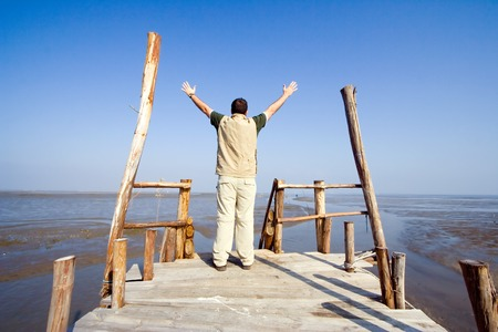 Man with his arms wide open on a dock Stock Photo - 1490863