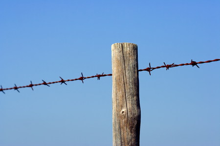 iron fence: Old fence post and barbed wire Stock Photo