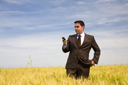 businessman at the phone in the field under blue sky Stock Photo - 3582968