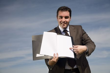 young businessman with corporate binder pointing to blank paper - outdoor environment Stock Photo - 3582886