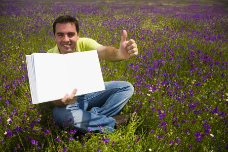 Young Man in a flied Holding Open Book with Blank Pages photo