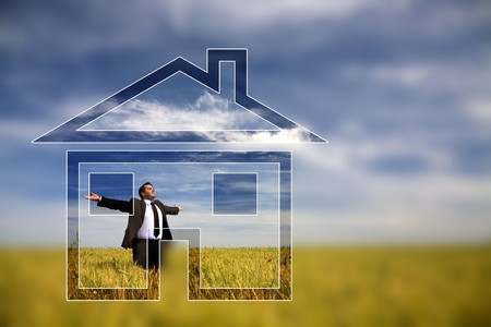 businessman with his arms wide open in rural field with dream house photo