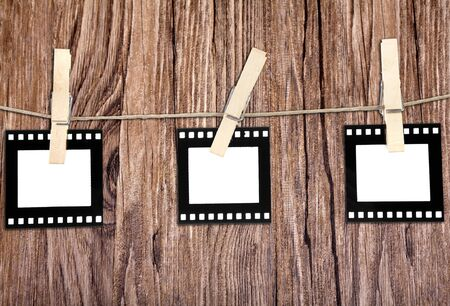 old film blanks hanging on a rope held by clothespins over wood background Stock Photo
