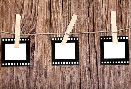 lembo: vecchia pellicola vuoti, appesa a una corda detenuta da clothespins su sfondo di legno