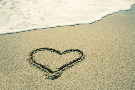 handwritten heart on sand with wave approaching Stock Photo