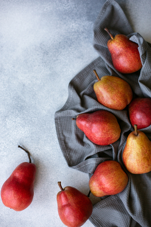 Beautiful pears on concrete table with grey kitchen towel. Close up. Autumn harvest. Copy space. Stock Photo