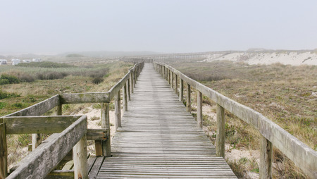 Wooden footbridge of Costa Nova beach in a foggy morning. Aveiro, Portugal