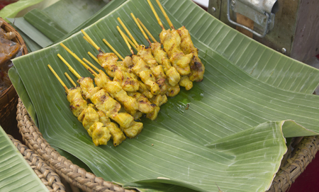 Appetizing Chicken Satay resting on banana leaves after being grilled, ready to be served at a street market.
