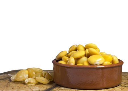 Earthenware bowl full of salted lupin beans, sitting in marble top with lupini skins. White background with copy space.
