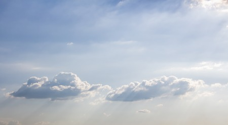 Sun shining on beautiful fluffy clouds in bright blue sky. Inspirational and peaceful background with copy space.