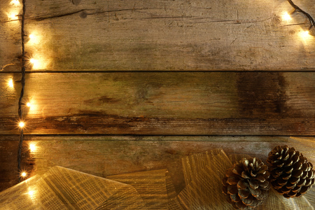 Flat lay of rustic wooden table, with Christmas lights, pine cones and golden wide stripe ribbon. With copy space.